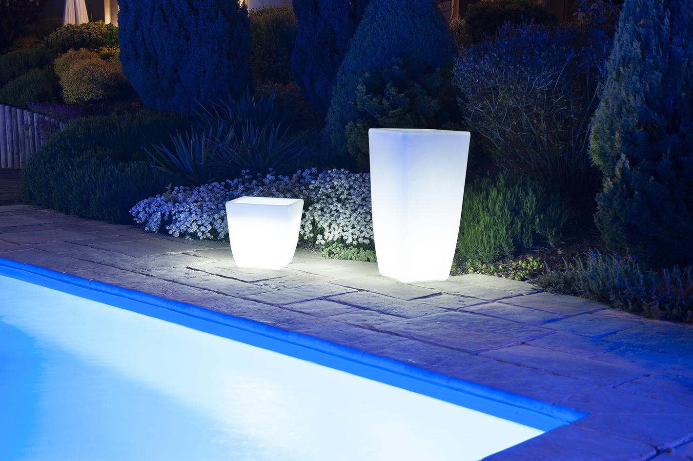 Un vase et pot lumineux à Led blanc au bord d'une piscine