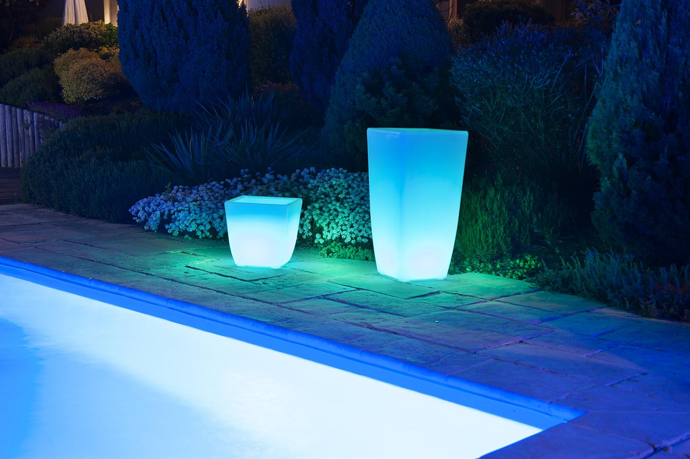Un vase et pot lumineux exterieur à Led bleu au bord d'une piscine