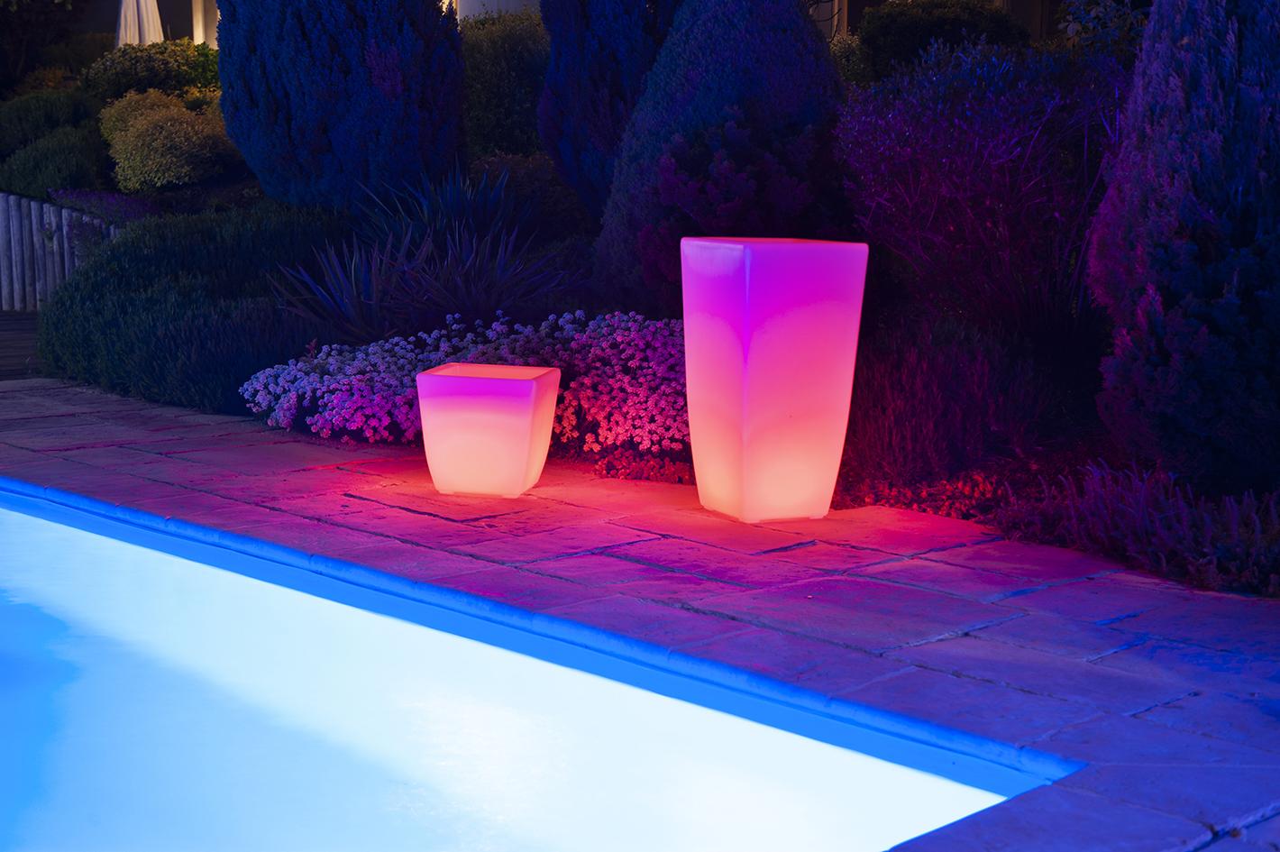 Un vase et pot lumineux à Led Rouge au bord d'une piscine