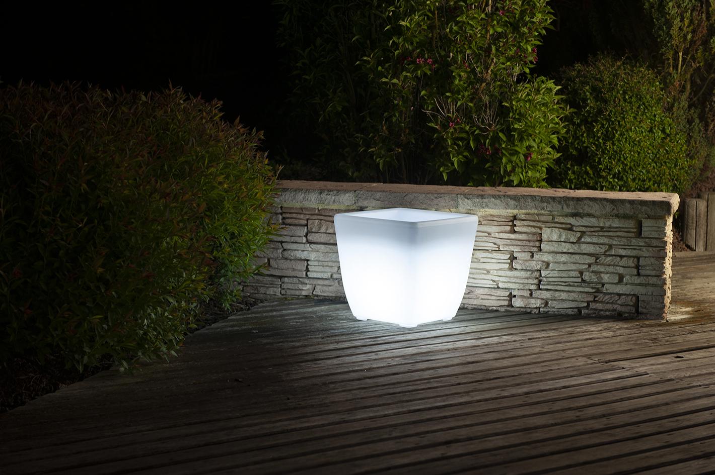 Un pot de fleur illuminé blanc sur une terrasse en bois